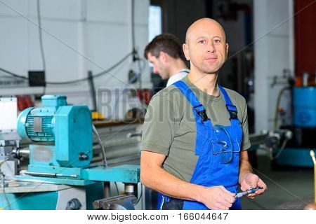 Worker In Factory On The Machine