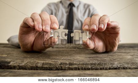 Hands Of A Businessman Holding Puzzle Pieces