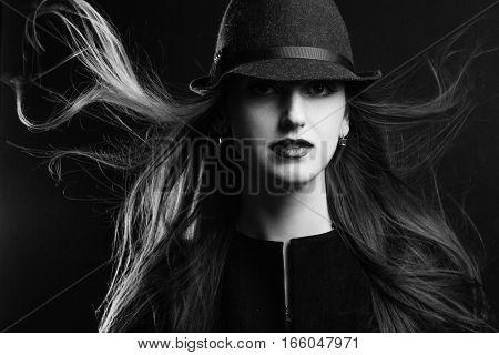 Portrait of the girl in studio. Model in elegant hat. Black and white.