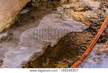 Stream that has partially frozen over with an irrigation hose in the middle of the stream