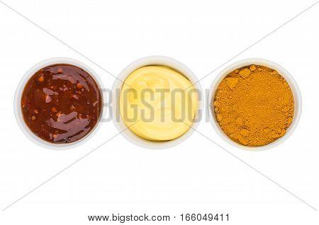 Tomato Ketchup, Mayonnaise And Turmeric In Glass Bowls