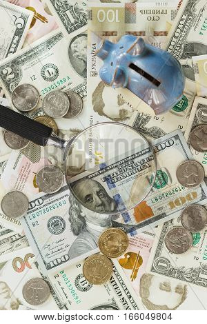 Ukrainian hryvnia and American's dollars with a magnifying glass soft focus background