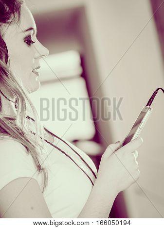 Woman With Headphones Choose Music On Smartphone.