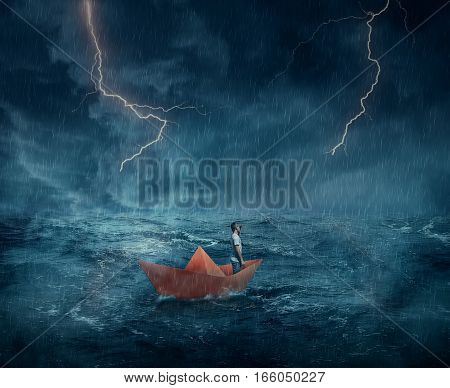 Young boy in a orange paper boat sail lost in the ocean in a stormy night with lightnings in the sky. Adventure and journey concept.