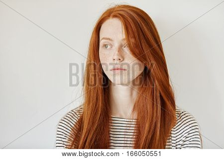 Portrait Of Cute Young Redhead Caucasian Woman With Freckles And Long Loose Hair Posing Isolated In