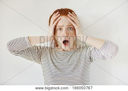 Close Up Portrait Of Puzzled And Scared Redhead Caucasian Student Girl Wearing Striped Top, Keeping