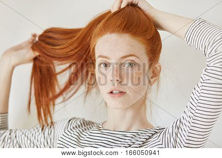 Youth, Tender Age And Lifestyle Concept. Fashionable Young Woman With Freckled Tying Her Beautiful G