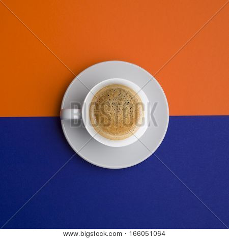 creative cup of coffee top wiev over orange and blue background