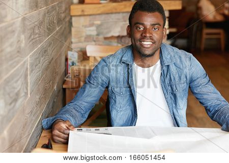 Handsome Young African Man Wearing Denim Jacket Over White T-shirt Sitting At Cozy Cafe, Holding New