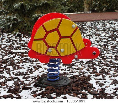 Empty turtle toy on playground in winter