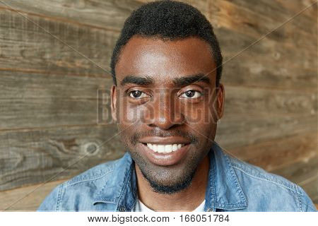 Headshot Of Attractive Young Dark-skinned Bearded Student In Stylish Jeans Shirt Smiling Cheerfully