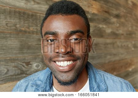 Close Up Shot Of Handsome African Student With Beard Dressed In Denim Shirt Smiling Happily, Showing