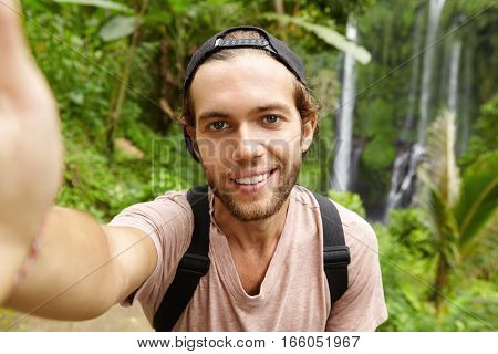 Close Up View Of Handsome Caucasian Hiker Wearing Snapback Looking At Camera With Happy Smile While