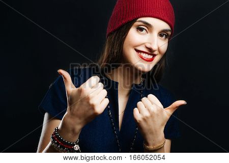 Portrait of pretty girl in red hat. She smiles very cheerful and points that all is good.