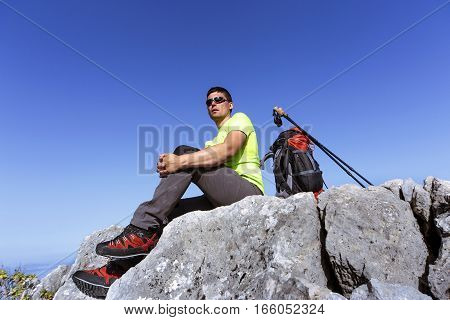 A man with a backpack hiking in the mountains on a sunny day.