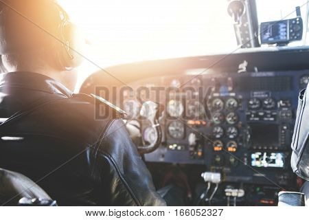 Adult Airplane Pilot Wearing Headset And Outfit Performing His Job, Sitting Inside Aircraft Cockpit
