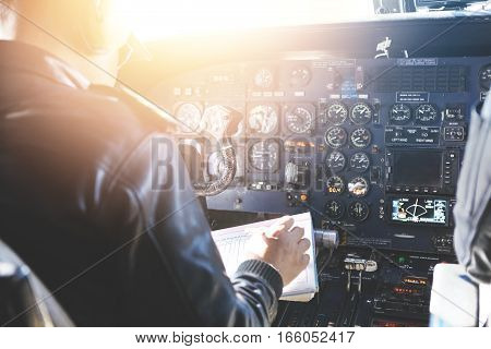 People And Occupation Concept. Adult Captain Of Jet Airliner Wearing Black Leather Jacket And Headse