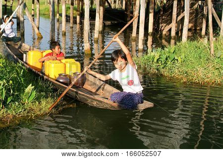 Maing Thauk (lake Inle) Myanmar - 15 January 2010: Children on rowing a boat at the village of Maing Thauk on lake Inle Myanmar