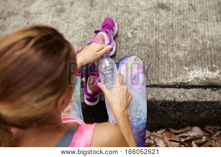 Top Shot Of Young Caucasian Athletic Girl In Space Print Leggings And Running Shoes Having Rest On S