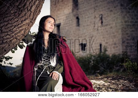 medieval lady posing in front of the ruins of 'burg reussenstein' in southern germany