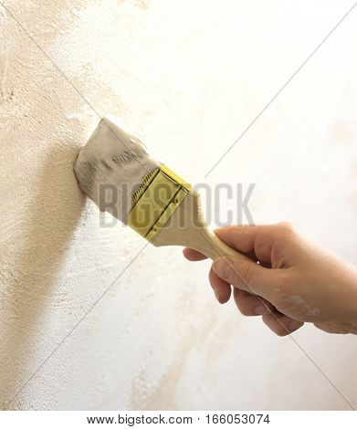 Woman's hand with brush painting wall repair vertical photo