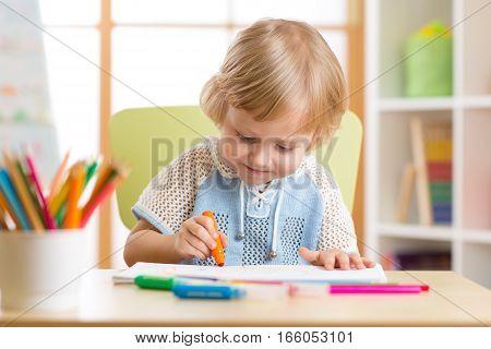 Cute little child is drawing with felt-tip pen in preschool