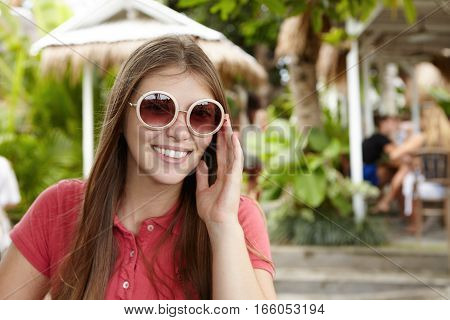 Outdoor Shot Of Beautiful Young Woman Adjusting Her Hipster Round Sunglasses And Looking At Camera W