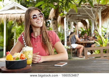 Fashionable Woman In Round Shades Smiling Happily While Having Breakfast At Sidewalk Restaurant, Sit