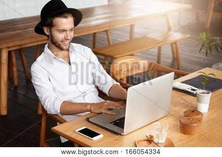 Indoor Shot Of Male Blogger Typing On Keyboard Of Laptop, Using Free Wi-fi At Modern Cafe While Work