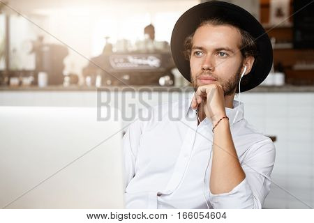 Pensive Young Bearded Businessman Wearing White Shirt And Black Hat Touching His Chin And Looking Ah