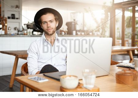Human, Modern Technology And Communication Concept. Handsome Young Student In Earphones Sitting At W