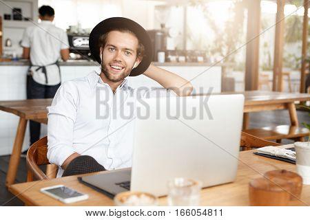 Modern Young Male In Trendy Headwear Having Fun Alone, Enjoying Leisure Time At Coffee Shop, Browsin