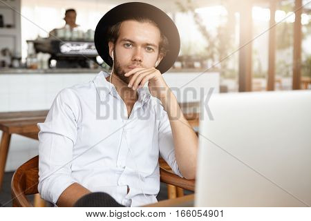 Pensive Bearded Student In Black Hat Holding Hand On His Chin Sitting In Front Of Open Laptop Comput