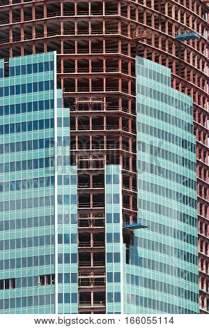 Mid section of multi-storey building constructing with glass panels cover close up