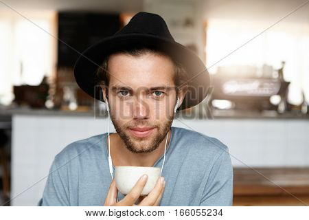Attractive Young Male In Black Headwear Holding Mug, Drinking Tea Or Coffee And Listening To Music O