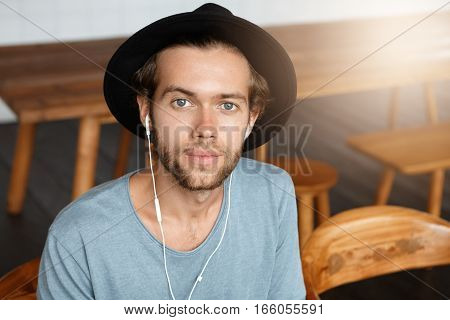 Indoor Portrait Of Fashionable Young Bearded Hipster In Trendy Hat Sitting On Wooden Chair At Modern