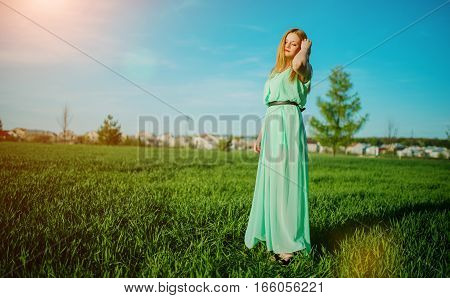 Woman In A Beautiful Long Turqoise Dress Posing On A Meadow On Grass.