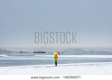 Lonely woman standing on sea shore with bright umbrella and dreaming of summer