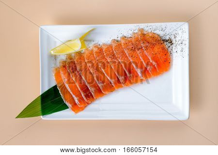 Sliced red fish fillet on white sqare dish