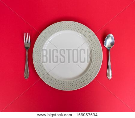 Empty dish spoon and fork on pink background