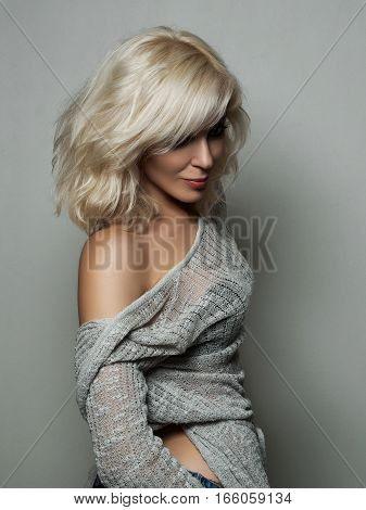 Beautiful blonde woman posing over gray background