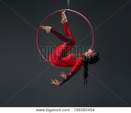 Young brunette girl in artistic embroidered red and black sportsuit exercising with a hoop studio shot