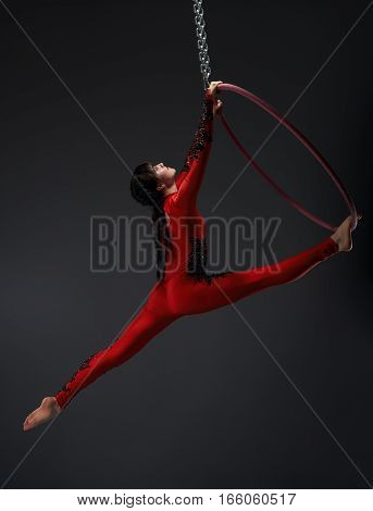 Pretty brunette girl in artistic embroidered red and black sportsuit exercising with a hoop studio shot