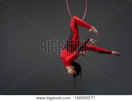 Young brunette girl in artistic embroidered red and black sportsuit exercising with a hoop studio portrait