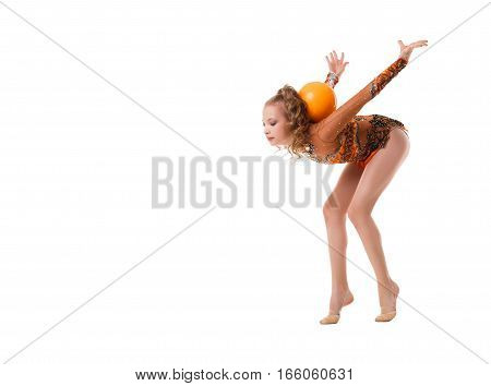 Young blonde girl in artistic embroidered sportsuit exercising with a yellow ball studio shot