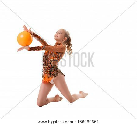 Young blonde girl in nice artistic embroidered sportsuit exercising with a yellow ball staying on her knees studio shot