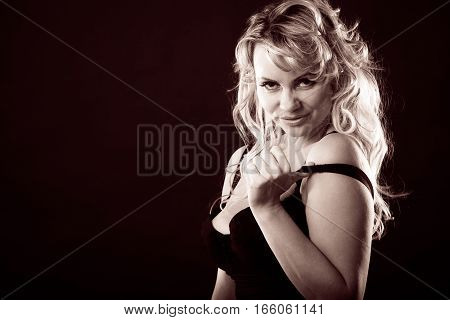 Sexiness of women. Attractive sensual blonde adult woman in black on dark background. Sexy lady wearing lingerie.