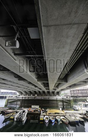 South Boston, Massachusetts, USA - July 7, 2016: Massive underpinnings of Seaport Boulevard bridge provide shelter for small boats in Fort Point Channel