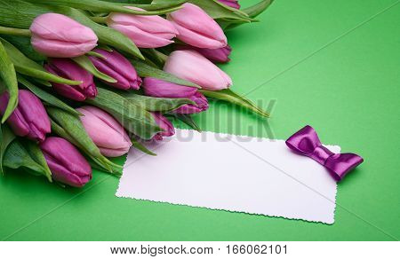 Greeting card, bouquet of beautiful flowers, buds of spring tulips, bow from satin ribbon, the gift set on a green background