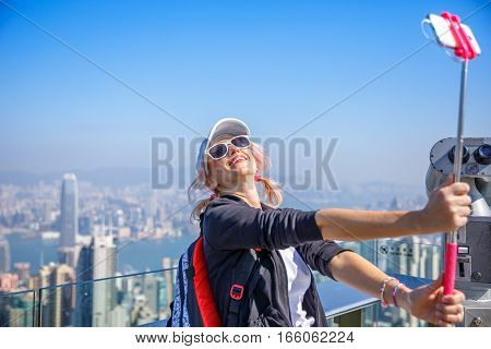 Hong Kong Victoria Peak tourist taking selfie stick picture photo with smartphone enjoying view over Victoria Harbour. Young happy woman travel in Asia.Viewing platform on top of Peak Tower, Hong Kong